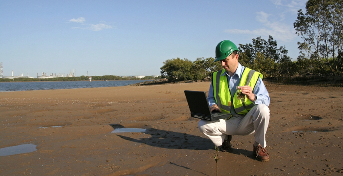 An environmental scientist stood on mudflats analysing data on his laptop.